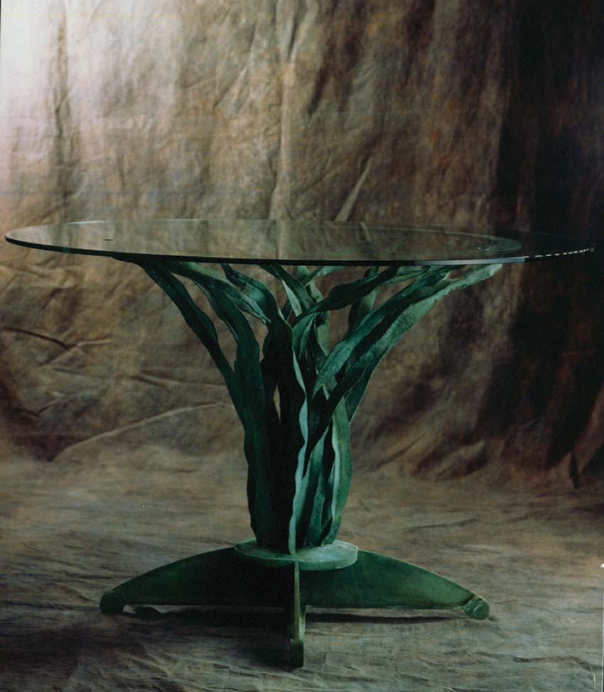 Forged bronze and glass table. Artist: Antony Donaldson